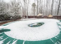 Inground swimming pool with cover on it and water pump during a snowfall in winter,